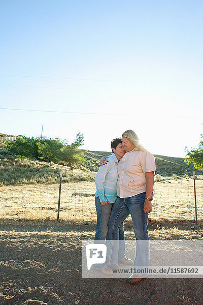 Reifes lesbisches Paar umarmt sich auf der Ranch