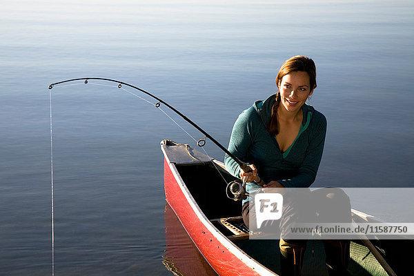 Frau beim Fischen vom Kanu aus