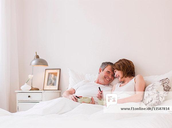 Älteres Ehepaar beim Essen im Bett