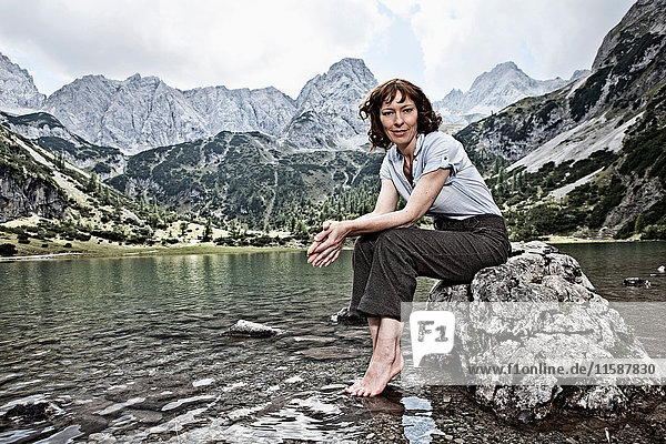 Woman in bare feet sitting by lake