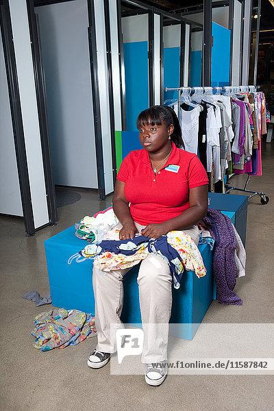 Junge Frau sitzt in der Umkleidekabine eines Bekleidungsgeschäfts
