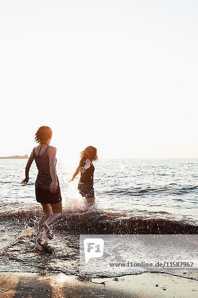 Frauen spielen in Wellen am Strand