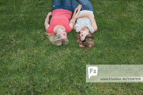 Junges lesbisches Paar liegt zusammen auf Gras