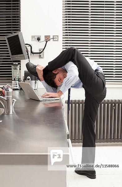Geschäftsmann  der sich in der Küche räkelt