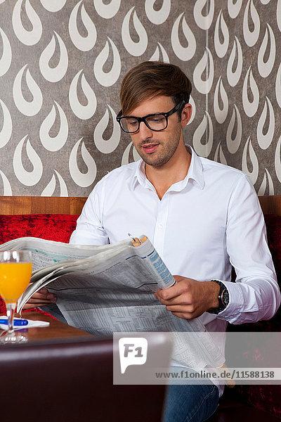 Mann liest Zeitung im Cafe