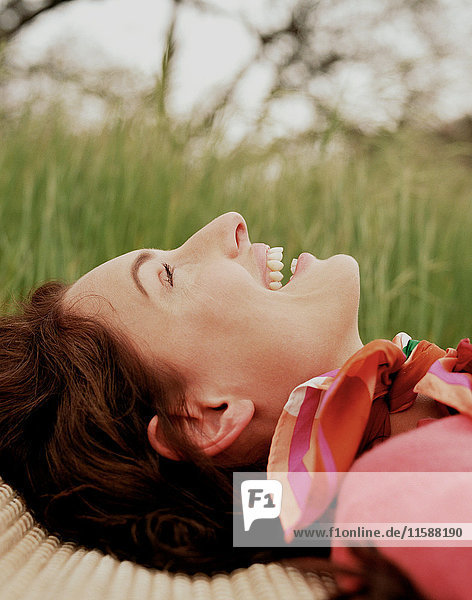 Frau lächelnd im Gras liegend