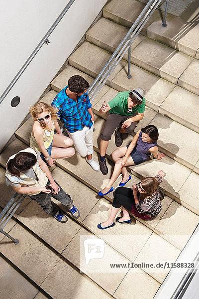 Gruppe junger Leute auf Stufen sitzend