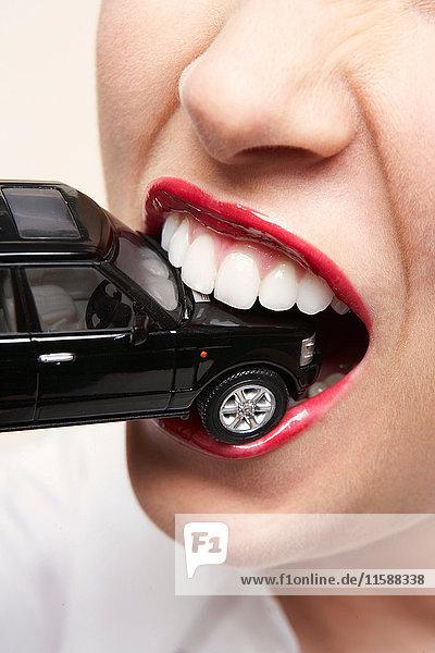 Woman biting toy car
