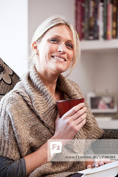 Mittlere erwachsene Frau mit Becher  lächelnd