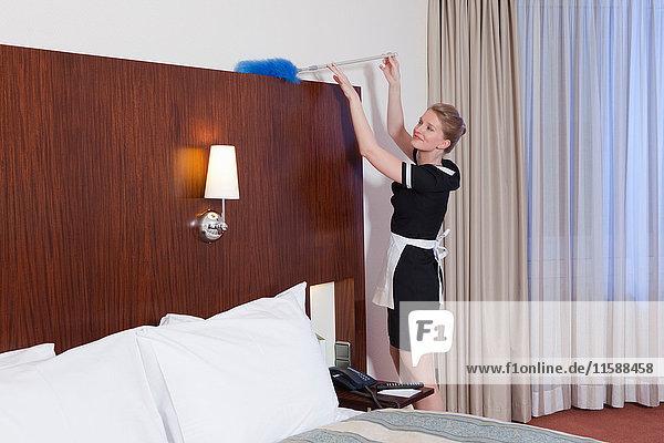 Zimmermädchen staubt Bett ab  lachend