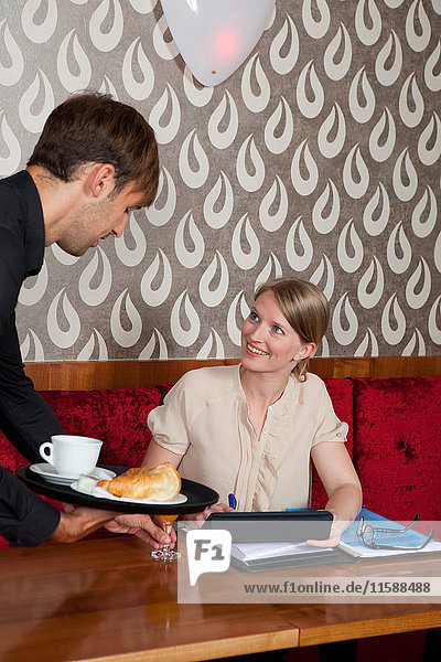 Waiter serving woman in cafe