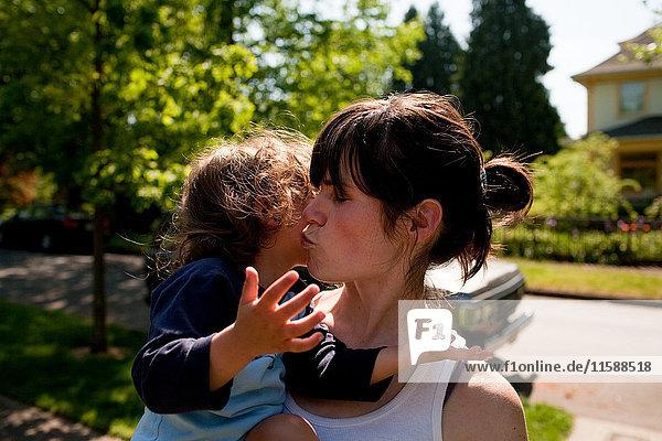 Mutter küsst Kleinkind-Tochter