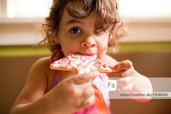 Mädchen isst sternförmigen Keks
