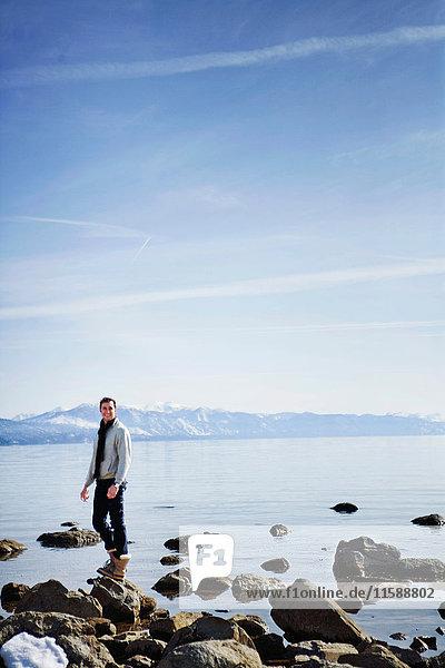 Mann steht auf Felsen in der Nähe des Sees