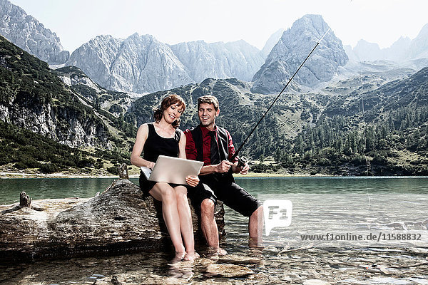 Paar fischen und Laptop benutzen am See