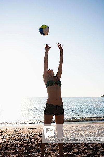 Frau spielt mit Volleyball am Strand