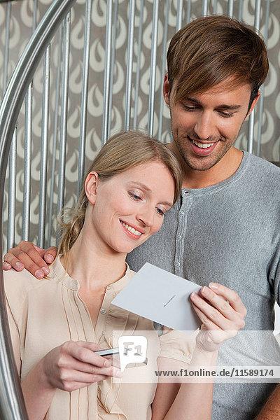 Lächelndes Paar bewundert Postkarte