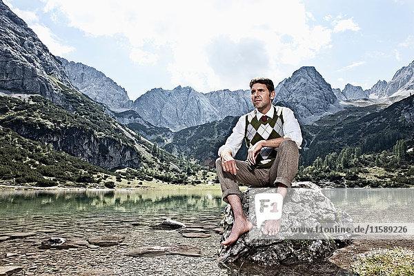 Barfüssiger Mann am See sitzend