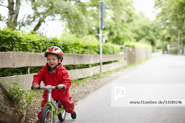 Smiling boy riding bicycle outdoors