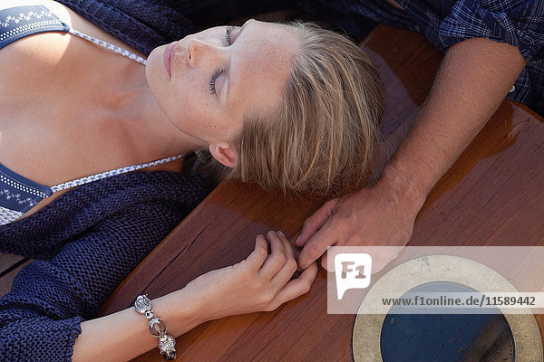 couple lying on deck holding hands