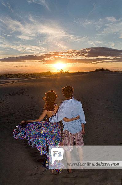 Paar beobachtet Sonnenuntergang am Strand