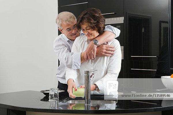 Mann umarmt Frau beim Abwasch