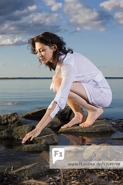 Woman in white dress crouching on rocks by sea