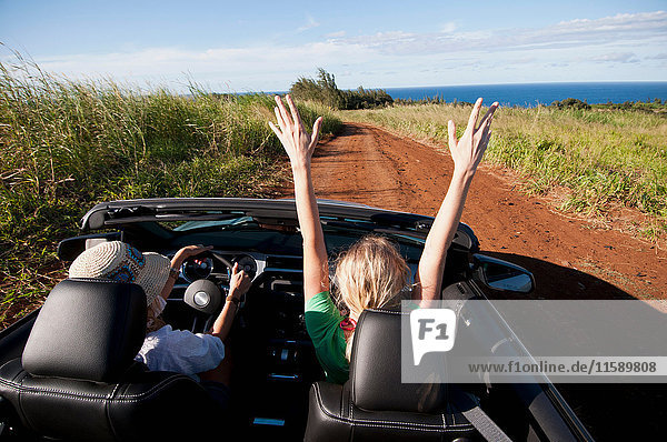 Women driving convertible on dirt road