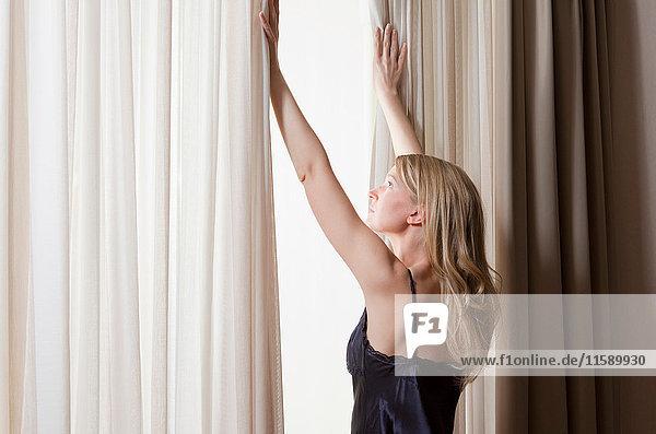 Frau im Negligee öffnet Vorhang