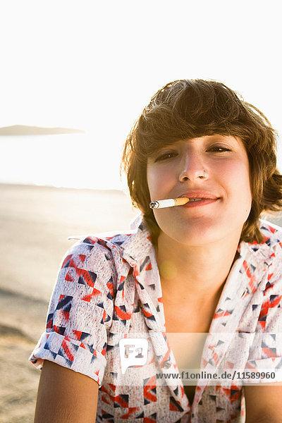 Frau raucht Zigarette am Strand