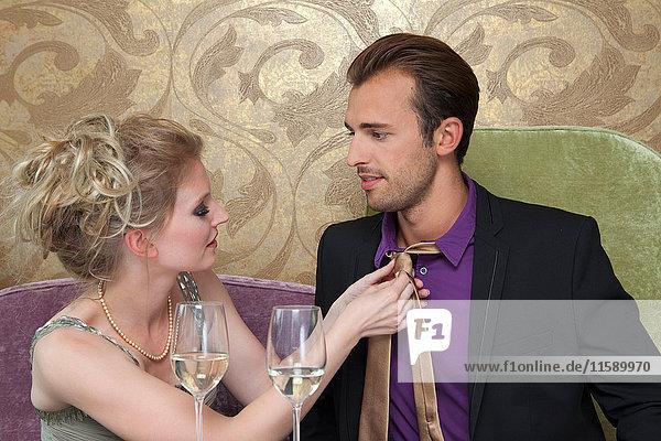 Frau  die die formelle Krawatte ihres Freundes repariert.