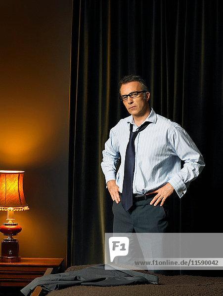 Mann mit Brille steht im Schlafzimmer