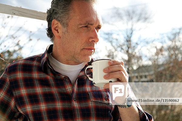Reifer Mann trinkt draußen aus der Tasse