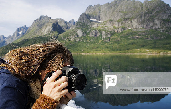 Woman taking a photograph in mountain landscape