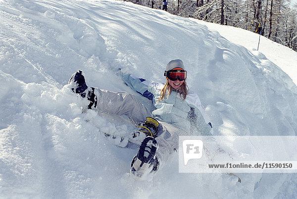 Mädchen rollt im Schnee