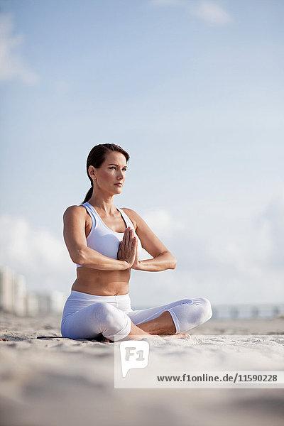 Frau praktiziert Yoga am Strand