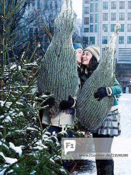 Ein Paar kauft Weihnachtsbäume