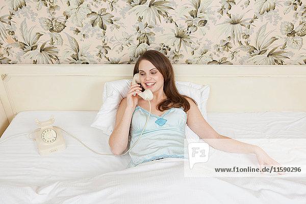 junge Frau im Bett am Telefon  glücklich