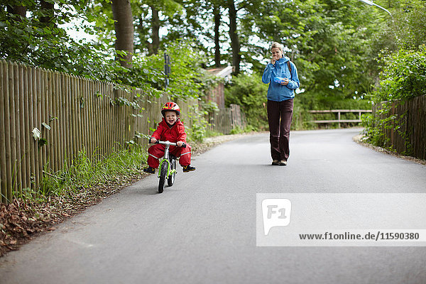 Mother watching son ride bicycle