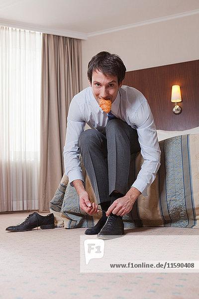 Mann isst  während er seine Schuhe zubindet