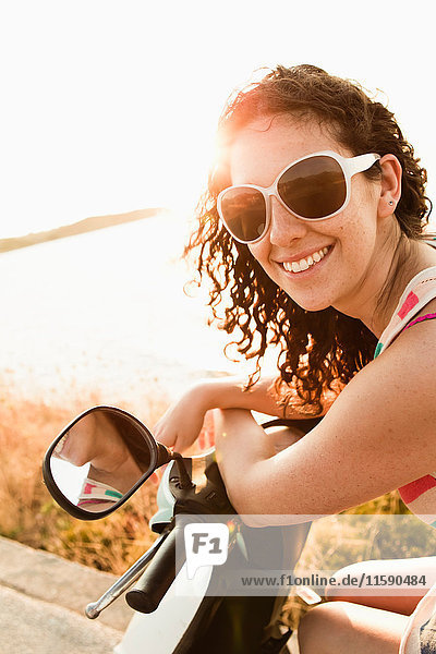 Smiling women riding scooter