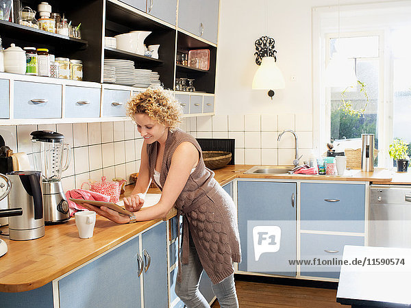 Mid adult woman using tablet in kitchen