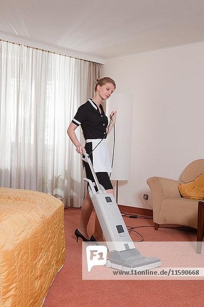Zimmermädchen beim Staubsaugen im Hotelzimmer