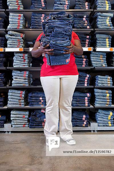 Junge Frau trägt einen Stapel Jeans im Kleidergeschäft