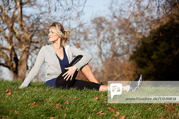 Mittlere erwachsene Frau bei Aufwärmübungen im Park