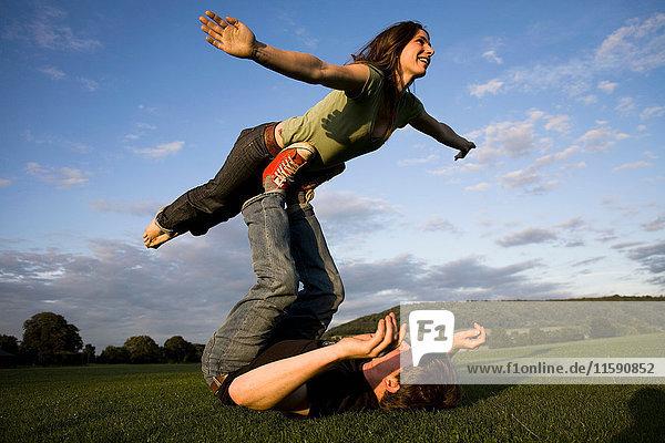 Man balancing girlfriend on his feet