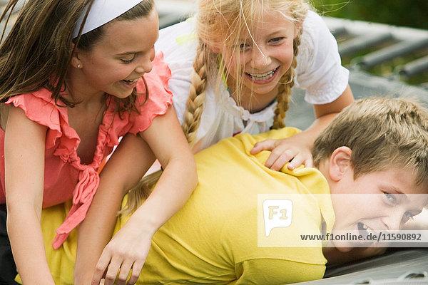 2 junge Mädchen ringen mit einem kleinen Jungen