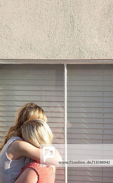 Junges lesbisches Paar umarmt sich am Fenster