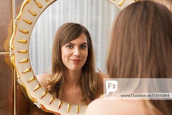 Frau vor dem Spiegel  lachend