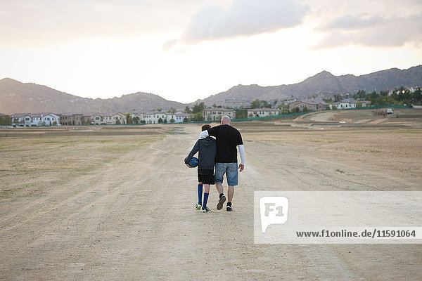 Father and son walking away